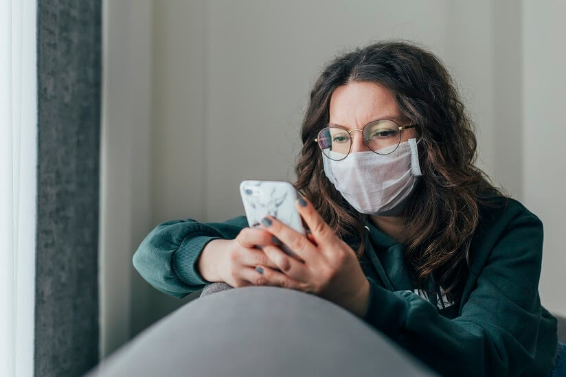 woman wearing a mask and looking at her phone